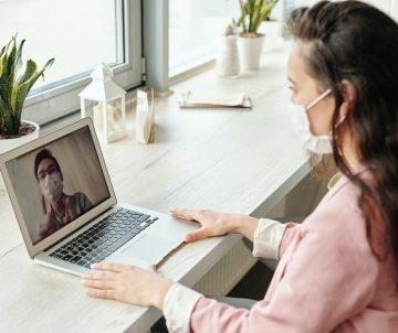 Frau mit Maske am Laptop
